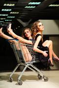 Enigmatic girls with shopping trolley - stock photo