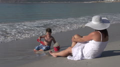 Young boy playing on the beach while mother looks on, Cape Town,South Africa Stock Footage