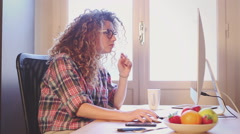 Young woman working at home or in a small office Stock Footage