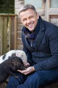 Mature Man Feeding Pet Micro Pig - stock photo