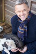 Mature Man Feeding Pet Micro Pig Stock Photos