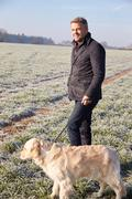 Mature Man Walking Dog In Frosty Landscape - stock photo