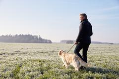 Mature Man Walking Dog In Frosty Landscape Stock Photos