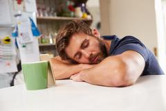 Tired Man Asleep At Kitchen Table Next To Mobile Phone - stock photo