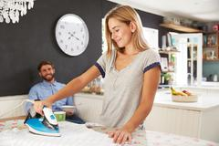 Woman Irons Shirt Whilst Man Eats Breakfast - stock photo