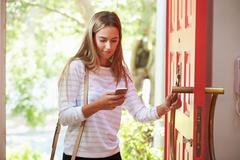 Young Woman Returning Home For Work Looking At Mobile Phone - stock photo