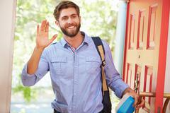 Young Man Leaving Home For Work With Packed Lunch - stock photo