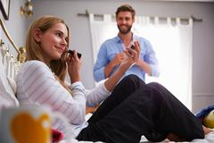 Woman Puts On Make Up As Man Gets Dressed In Bedroom Stock Photos