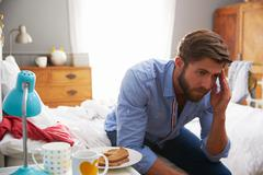 Man Suffering From Depression Sitting On Edge Of Bed Stock Photos