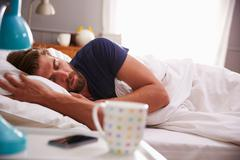 Stock Photo of Sleeping Man Being Woken By Mobile Phone In Bedroom