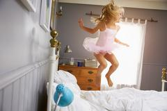 Girl In Ballerina Outfit Jumping On Parents Bed Stock Photos
