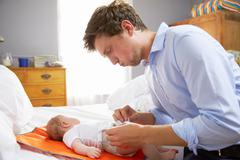 Father Dressed For Work Changing Baby's Diaper In Bedroom Stock Photos