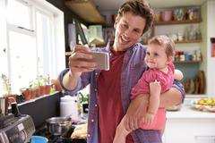 Father Cooks Meal Whilst Holding Young Daughter - stock photo