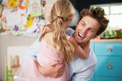 Daughter Hugging Father Returning From Work - stock photo