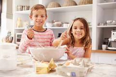 Two children having fun baking in the kitchen - stock photo