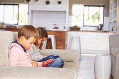 Kids playing with new technology while adults entertain - stock photo