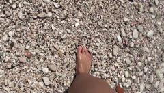 Walking on pebbles along the sea brim - stock footage