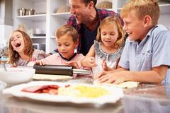 Father making pizza with his kids Stock Photos