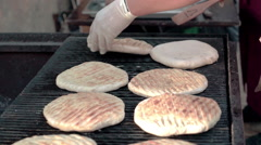 Cook preparing pieces of homemade bread on grill. Street food festival. Stock Footage