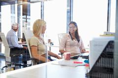 Happy colleagues talking in an office Stock Photos