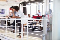 Staff working in a busy office mezzanine - stock photo