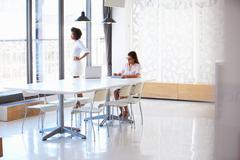 Two women working with digital tablet in empty meeting room Stock Photos