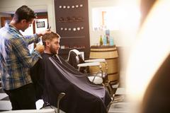 Male Barber Giving Client Haircut In Shop Stock Photos