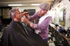 Male Barber Giving Client Shave In Shop - stock photo