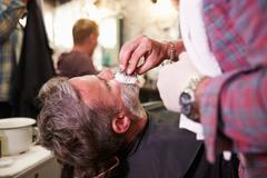 Male Barber Preparing Client For Shave In Shop - stock photo