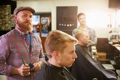 Portrait Of Male Barber Giving Client Haircut In Shop Stock Photos
