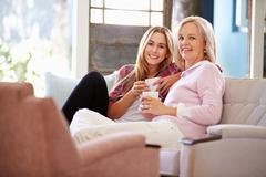 Mature Mother With Adult Daughter Relaxing On Sofa At Home - stock photo