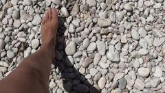 Walking on pebbles and entering the sea Stock Footage