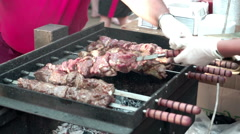 Cock preparing pieces of roasted shashlik beef meat on grill. Street food. Stock Footage