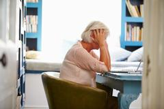 Stressed Senior Woman At Desk In Home Office With Laptop - stock photo