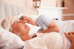 Worried Senior Woman Lying Awake In Bed Stock Photos