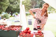 Woman Juicing Fresh Pomegranates At Farmers Market Stall - stock photo