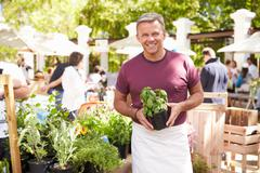 Man Selling Herbs And Plants At Farmers Food Market - stock photo