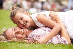 Mother And Daughter Relaxing At Outdoor Summer Event Stock Photos