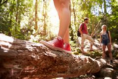 Close Up Of Feet Balancing On Tree Trunk In Forest - stock photo