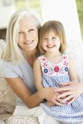 Portrait Of Grandmother And Granddaughter Sitting In Chair Stock Photos