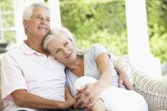 Senior Couple Relaxing On Seat Outside House Stock Photos