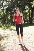 Young Woman Running Along Woodland Path - stock photo