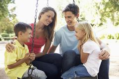 Family Sitting On Swing In Playground Stock Photos