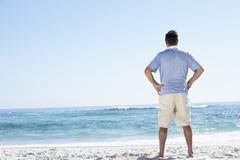 Senior Man On Holiday Standing On Sandy Beach - stock photo