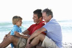 Grandfather With Grandson And Father Embracing On Beach Holiday Stock Photos
