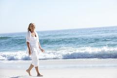 Woman Walking along Sandy Beach - stock photo