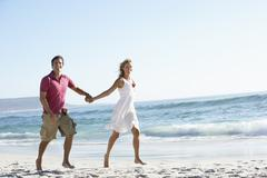 Young Couple Walking Along Sandy Beach On Holiday - stock photo