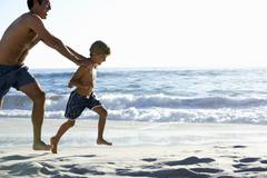 Father And Son Running Along Beach Together Wearing Swimming Costumes - stock photo