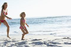 Mother And Daughter Running Along Beach Together Wearing Swimming Costume Stock Photos