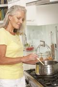 Senior Woman Preparing Meal At Cooker Stock Photos